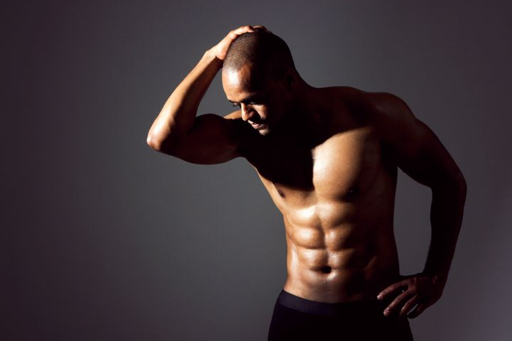 Young black man flexing abs. Dramatic lighting.