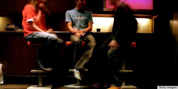 Three men sitting on bar stools in Freedom Cafe., Soho, London, London, England.