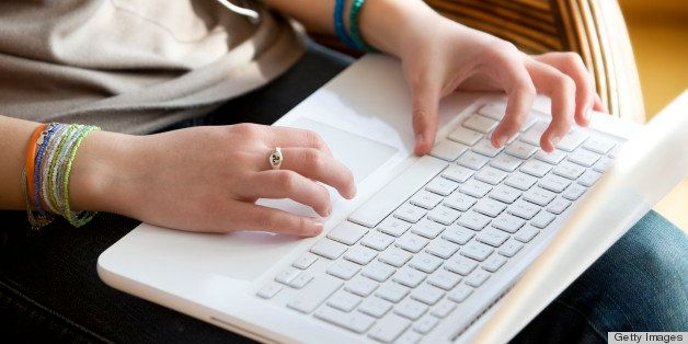 Close-up on teenager's hands typing on laptop's keyboard.