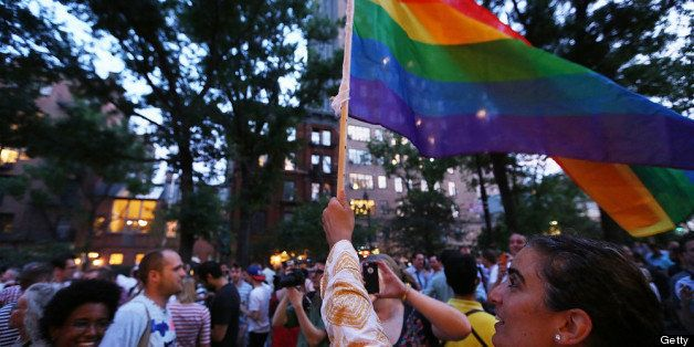 NEW YORK, NY - JUNE 26:  A woman waves a rainbow flag after the Supreme Court ruled key portions of the Defense of Marriage A