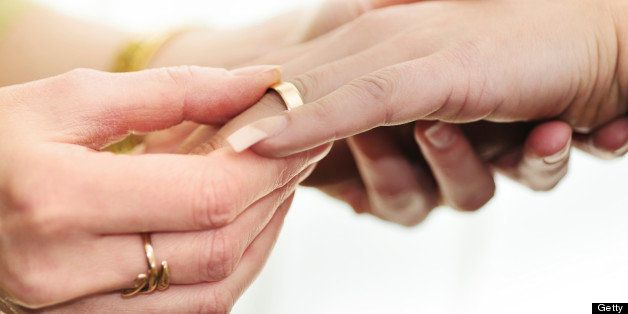 Woman's hand putting wedding ring on her female partner's hand in a wedding ceremony