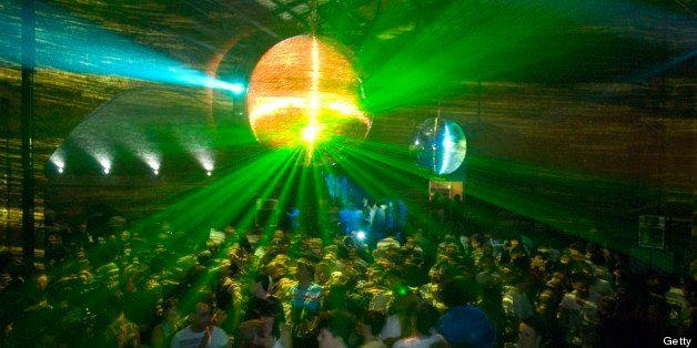 Mirrorball reflecting lights above crowded dancefloor. London 26.07.09