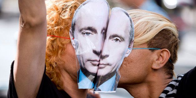Demonstrators wearing masks depicting Russian President Vladimir Putin kiss as they take part in a rally in front of the Russ