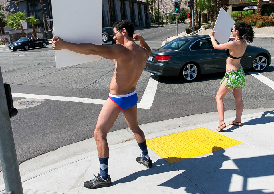 Performer Lupe Viscara of Magnificent 7 Male Revue and model Sara Chavez of Los Angeles invite cars at the corner of Ramon Rd