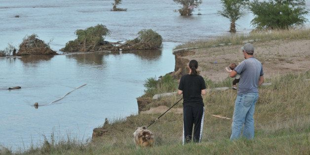 EVANS, CO - SEPTEMBER 17:  Family members look over a flooded field September 17, 2013 near Evans, in eastern Colorado. Even