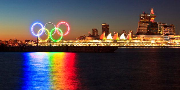 The Olympic Rings light up Coal Harbor/Harbour in front of Canada Place and downtown Vancouver at dawn. Vancouver British Col