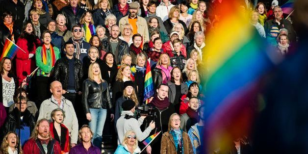 A crowd of people sing the Russian National Anthem at the Stockholm Olympic Stadium on October 6, 2013 while raising rainbow