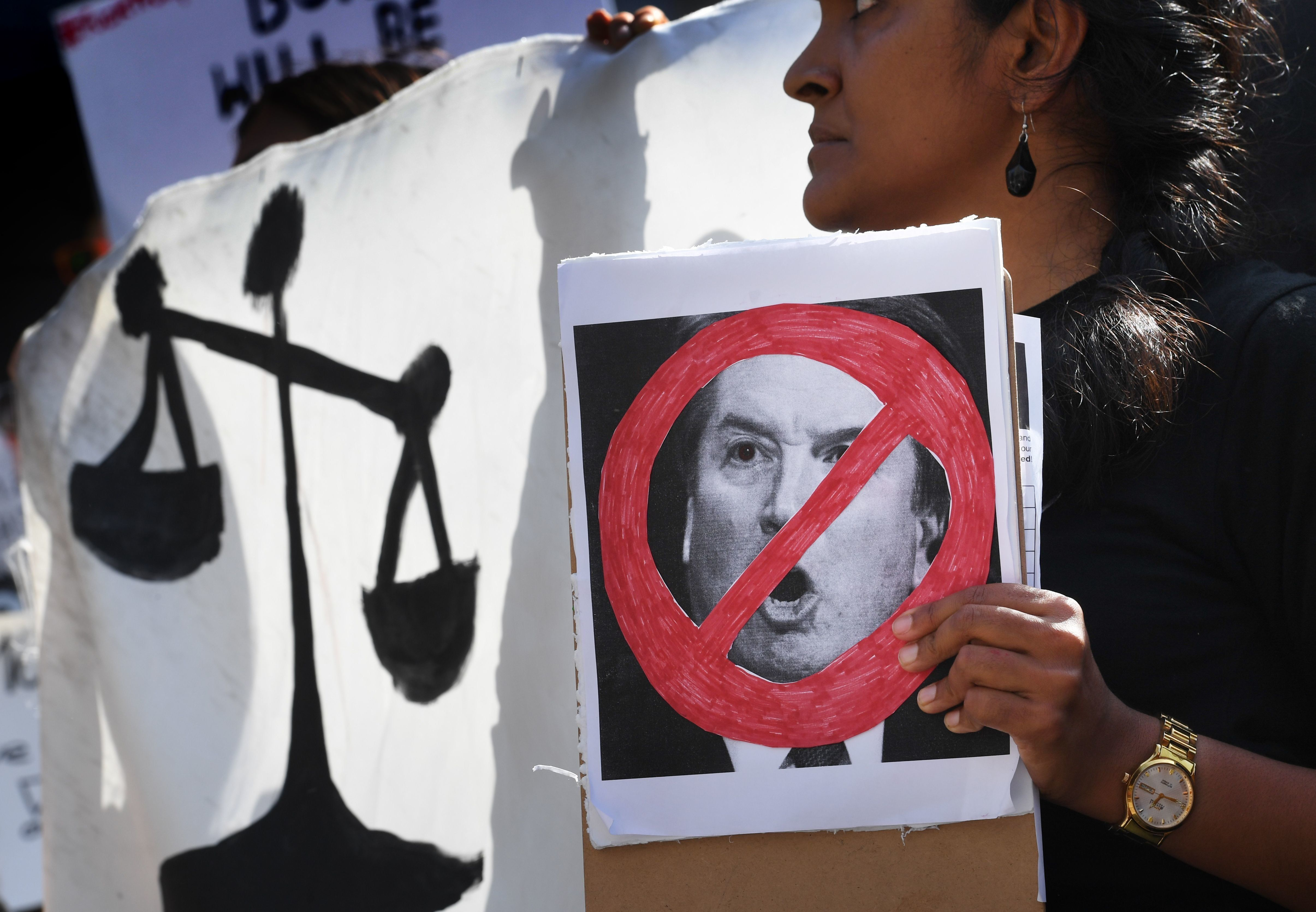Demonstrators hold anti-Kavanaugh hold banners outside City Hall in Los Angeles on September 28, 2018. - The Senate Judiciary Committee on Friday approved Brett Kavanaugh, Donald Trump's pick for the US Supreme Court, one day after he fought off allegations of sexual assault at an emotional day-long public hearing. But in a dramatic last-minute move, Republican Senator Jeff Flake of Arizona asked for a delay of up to a week before the full vote takes place to allow for an FBI investigation into the allegations against Kavanaugh. (Photo by Mark RALSTON / AFP)        (Photo credit should read MARK RALSTON/AFP/Getty Images)