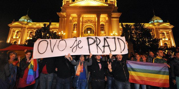 Gay rights activists hold a banner reading 'This is pride' as they demonstrate in front of the Serbian Parliament on late Sep