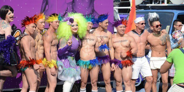 Attendees pose for photos during the annual gay parade in Taipei on October 26, 2013.  Tens of thousands of people rallied in