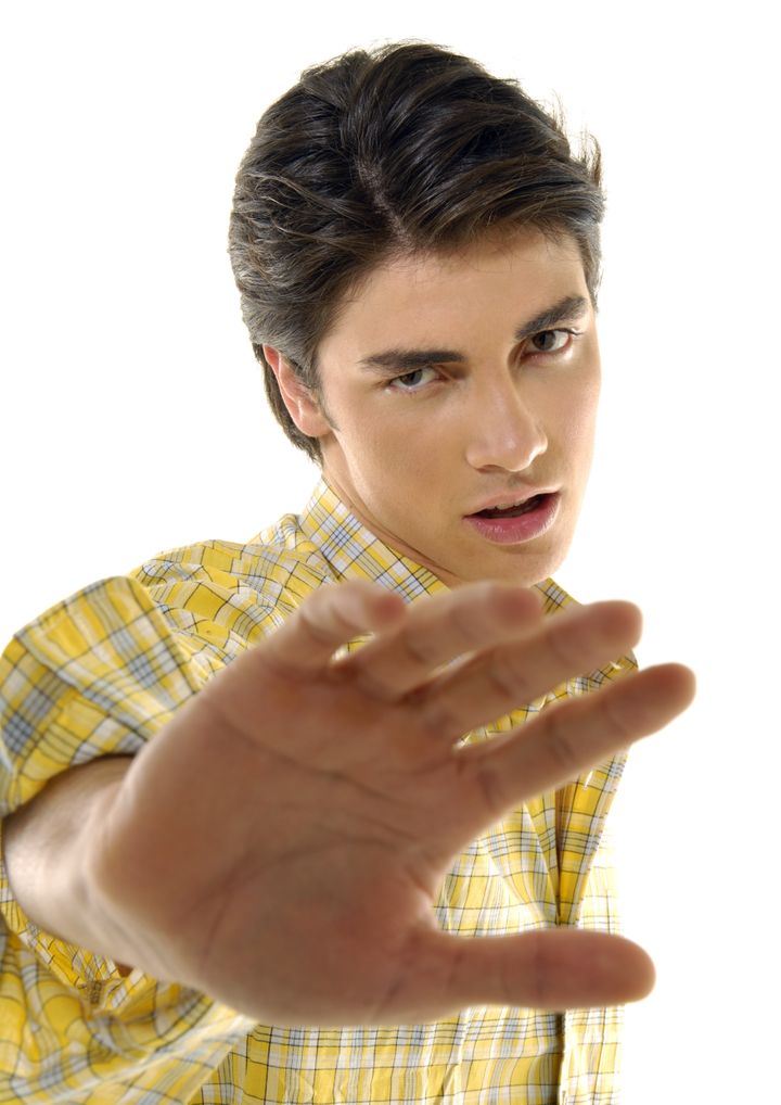 Portrait of a young man making a stop gesture