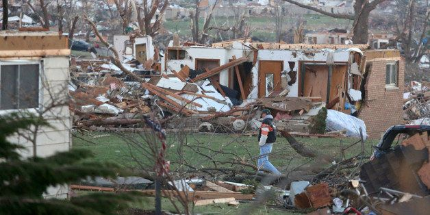 WASHINGTON, IL - NOVEMBER 18: A man walks amongst damaged buildings along Washington Road in the aftermath of a tornado on No