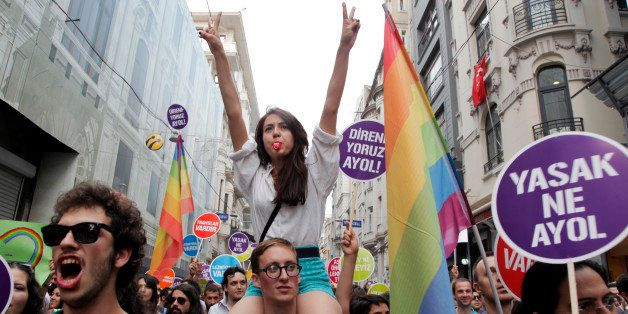 People march and chant slogans during a gay parade on Istiklal Street, the main shopping corridor on June 30, 2013 in Istanbu
