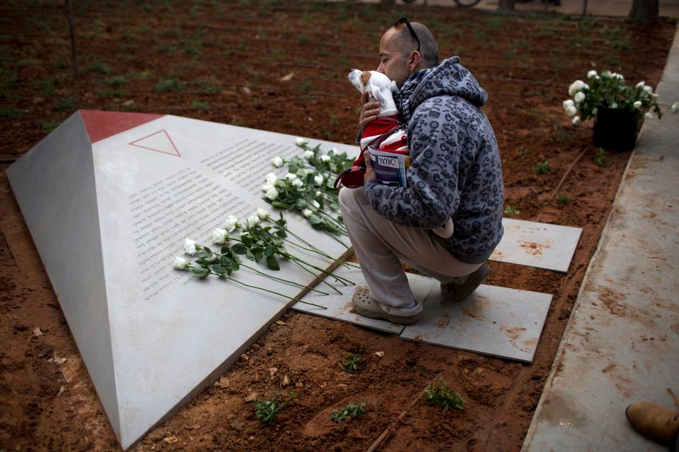 An Israeli man reads the text from a new monument honoring gays and lesbians persecuted by the Nazis during World War II for