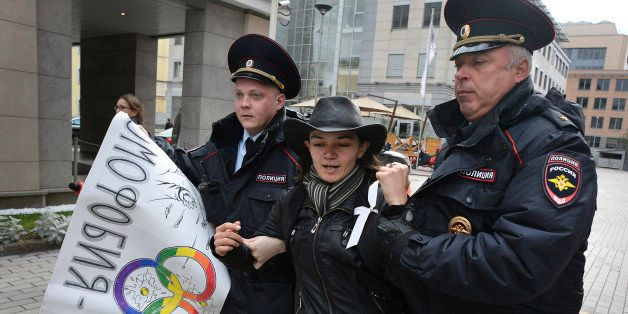 Police officers detain a gay rights activist during an unauthorized protest against hotly disputed Russian laws banning the p