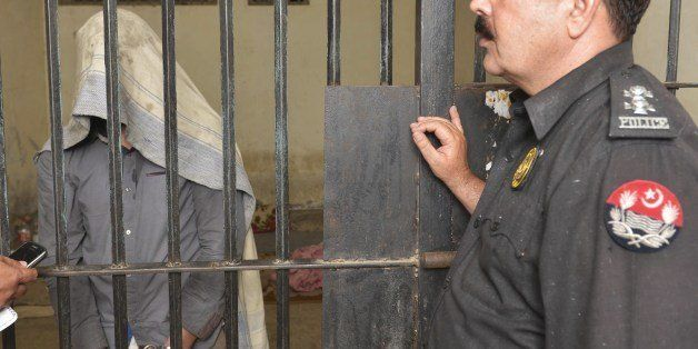 A Pakistani police officer presents a man arrested on charges of killing homosexual men, at a police station in Lahore on Apr