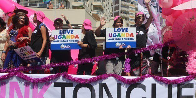 People stand on a float holding signs saying 'Love Uganda, hate homophobia' in reaction to Uganda's law banning homosexuality