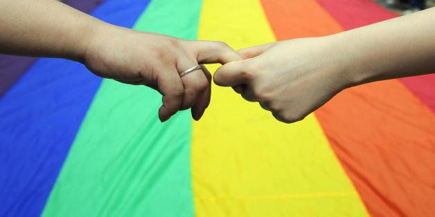 Gay and lesbian activists form a human chain around a rainbow flag during celebrations marking the fourth annual Internationa