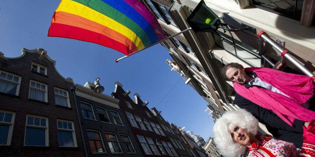 Former Amsterdam Mayor Job Cohen (R) walks in a street below a rainbow flag in Amsterdam, on April 7, 2013, prior to a protes