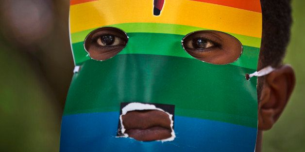 FILE - In this Monday, Feb. 10, 2014 file photo, a Kenyan gay wears a mask to preserve his anonymity as they stage a rare pro