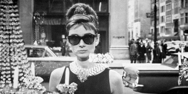 1961:  Belgian-born actor Audrey Hepburn (1929 - 1993), as Holly Golightly, holds a cup and a paper bag while looking into on