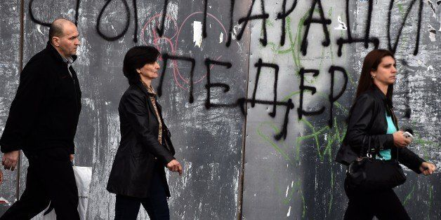 Pedestrian walk past a anti-gay graffiti, reading 'Stop the parade of fags', in Belgrade on September 26, 2014. Belgrade will