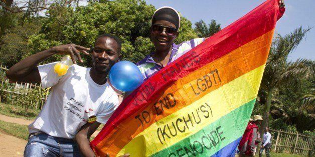 Ugandan men hold a rainbow flag reading 'Join hands to end LGBTI (Lesbian Gay Bi Trans Intersex - called Kuchu in Uganda) gen