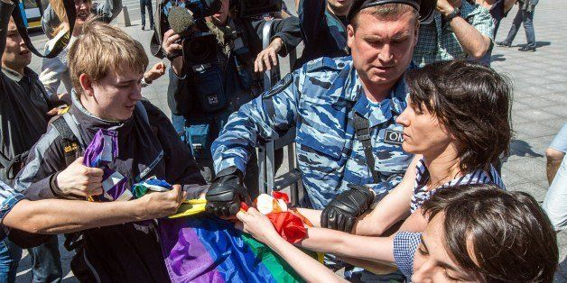 A man (L) takes away a rainbow flag as a policeman detain gay rights activists during their protest in central Moscow on May