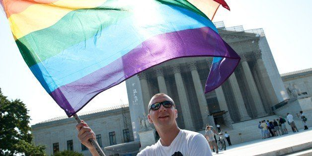 A gay rights activist waves a rainbow flag in front of the US Supreme Court in Washington,DC on June 25, 2013.   The high cou