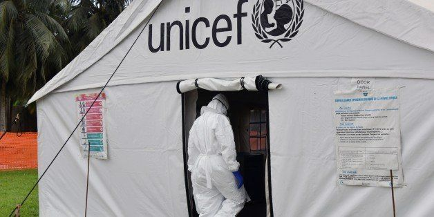 A man in full protective gear enters a tent in the Ebola treatment unit being preventively set to host potential Ebola patien