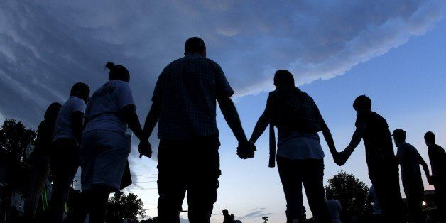 FILE - In this Aug. 20, 2014 fill photo people stand in prayer after march in Ferguson, Mo., to protest the shooting of Micha