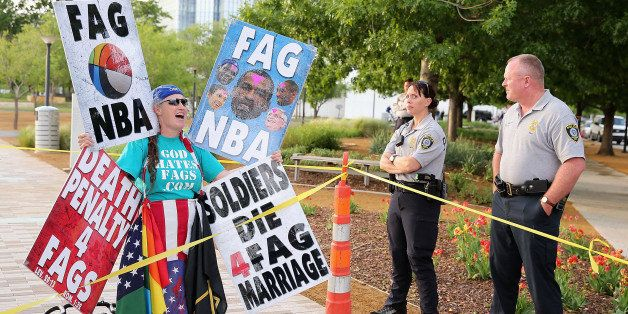 OKLAHOMA CITY, OK - MAY 01:  A member of the Westboro Baptist Church protests gay rights and the NBA as police officers look