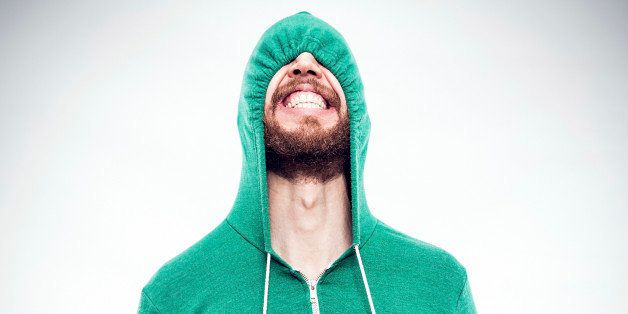 A bearded hipster young man pulls the drawstrings on his green hoodie, partially concealing the funny face he is making, comp