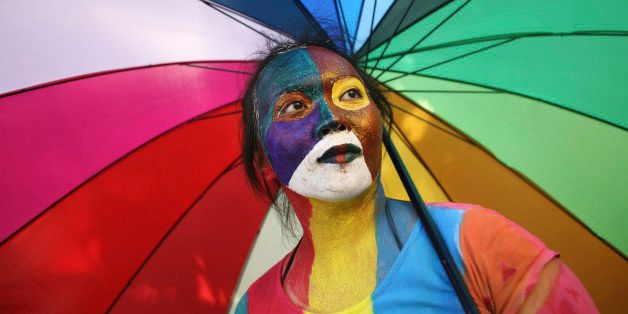 An Indonesian activist with painted face holds an parasol during a protest demanding equality for LGBTIQ (Lesbian, gay, bisex