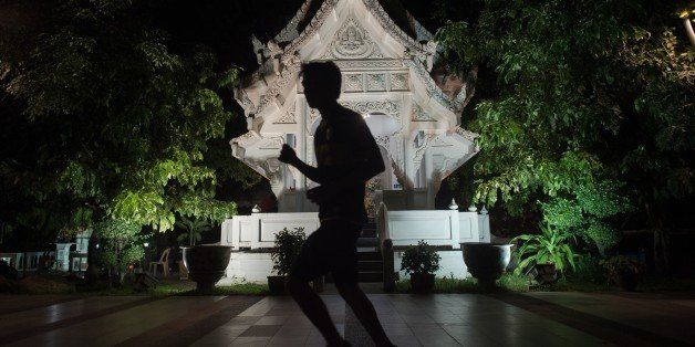 This picture taken on January 14, 2015 shows a man silhouetted as he jogs past an illuminated monument in Bangkok.    AFP PHO