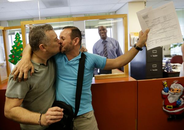 Jeff Ronci, 53, left, kisses his partner of 15 years, Juan Talavera, 46, as they hold up their marriage license at the Miami-
