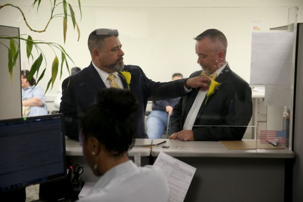 Carlos Noda (L) fixes the flower on the jacket of his husband to be Rich Matthews as they wait to get their marriage license
