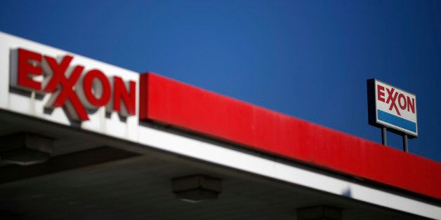 Signage is displayed at an Exxon Mobil Corp.  gas station stand Nashville, Tennessee, U.S., on Friday, Jan. 16, 2015. Trips t