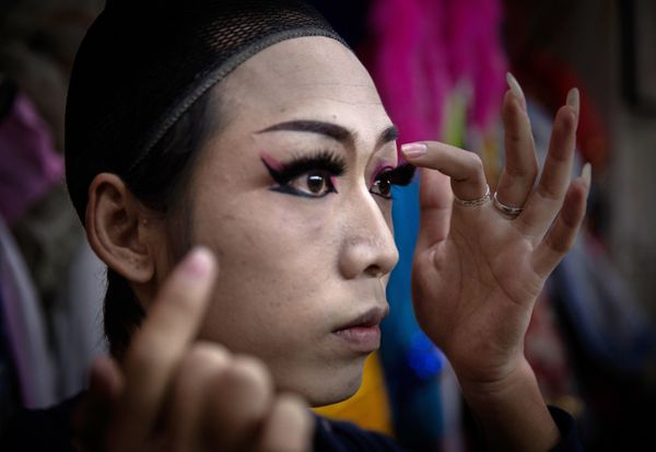 Chinese drag queen Caomei puts on fake eyelashes backstage before performing at the Chunai 98 club on January 10, 2015 in Nan