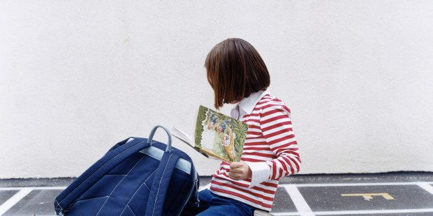 Girl (5-7) looking at book in playground