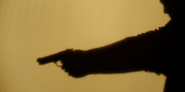 Shadow of man pointing gun, side view
