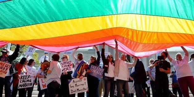 WASHINGTON, DC - APRIL 28:  Protesters hold pro-gay rights flags outside the US Supreme Court on April 28, 2015 in Washington