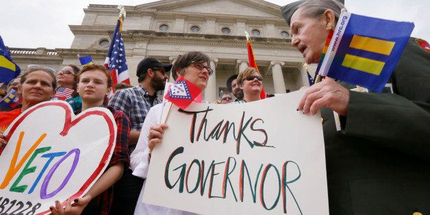 Kristen Hooper, center, and Robert Loyd, right, hold a sign on the steps of the Arkansas state Capitol thanking Arkansas Gov. Asa Hutchinson for calling for changes to a religious objection measure in Little Rock, Ark., Wednesday, April 1, 2015. The measure faced a backlash from businesses and gay rights groups. (AP Photo/Danny Johnston)