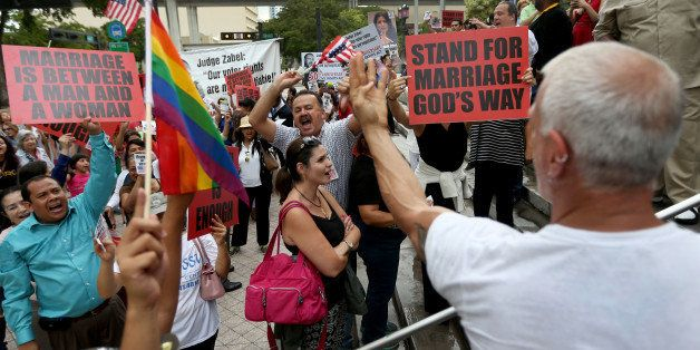 MIAMI, FL - JULY 02:  Opponents of same-sex marriage yell at Howard Brownstein, who is showing them his wedding ring, as he s