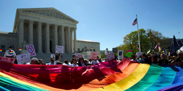 Demonstrators stand in front of a rainbow flag of the Supreme Court in Washington, Tuesday, April 28, 2015. The Supreme Court