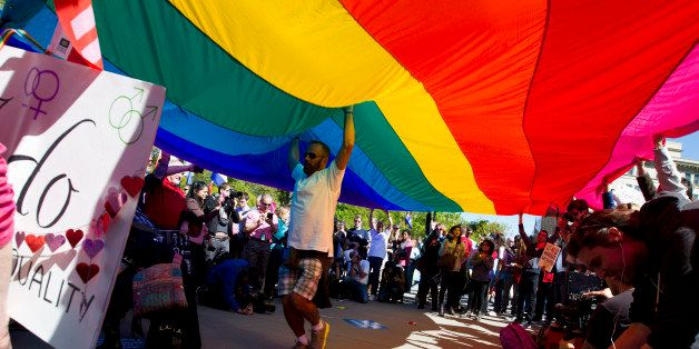 Demonstrators hold up a rainbow flag in front of the Supreme Court in Washington, Tuesday, April 28, 2015. The Supreme Court