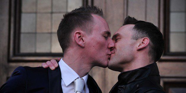 Tim Jarmaine-Groves (L) kisses his husband Richard Jarmaine-Groves after their same-sex wedding in north London on March 29,