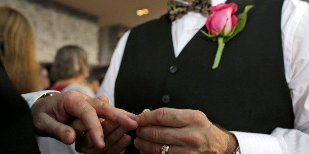 Steve Visano, 54, places a ring on his partner's hand during a group wedding ceremony at a hotel in honor of Florida's ruling