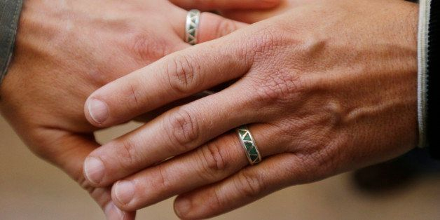 Army Capt. Michael Potoczniak, left, and Todd Saunders, of El Cerrito, Calif., show their wedding rings after they exchanged