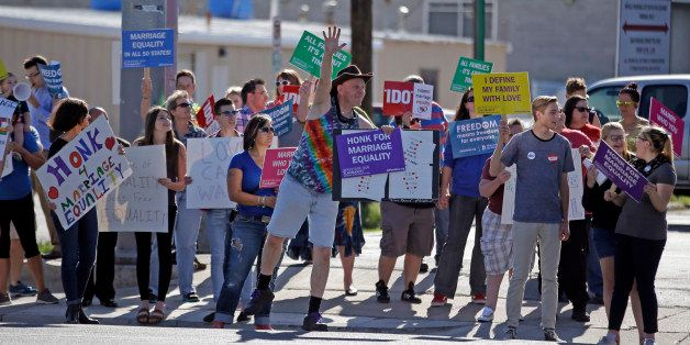 Same-sex marriage supporters hold signs encouraging drivers to honk in support of marriage equality during a rally Tuesday, A